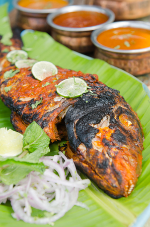 chaat: Grilled spicy fish tikka served with mint, lime, sauces and a banana leaf in a rustic setting.