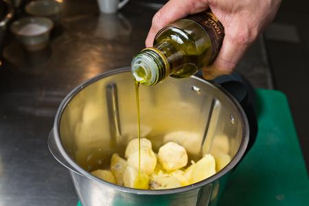 extra virgin olive oil: Extra virgin olive oil being poured onto peeled potatoes. Stock Photo