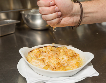 macaroni with cheese: Cooked breadcrumbs being sprinkled onto oven bake macaroni cheese. Stock Photo