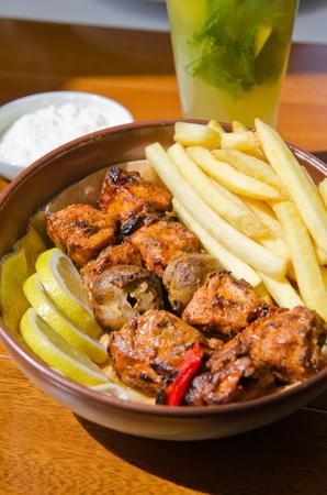 pollo rostizado: Kebab delicioso pollo a la parrilla, marinado en especias, servido con papas fritas, rodajas de lim�n, salsa de setas y pasta de s�samo.