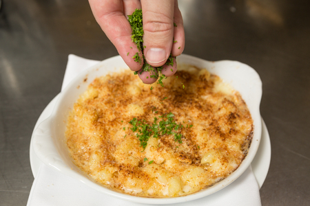 macaroni with cheese: Chopped fresh parsley being sprinkled onto oven baked macaroni cheese.
