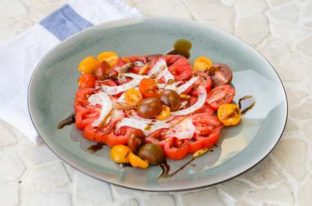 pine nut: A vibrant healthy mixed tomato, mozzarella, pine nut and balsamic vinegar salad, served on a rustic plate on a tile table.
