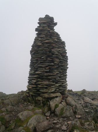 rock pile: A milestone rock pile on the top of a foggy mountain