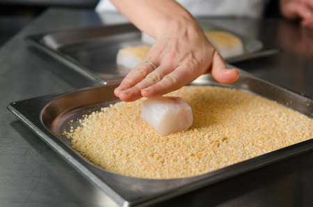 chippy: Fresh fish fillet cube being placed into breadcrumbs,before being pan fried.