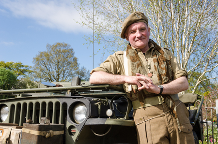militant: Yorkshire, England, 05152015, An british war veteran soldier with a beret hat leaning agains an army jeep. Howarth 1940s weekend Editorial