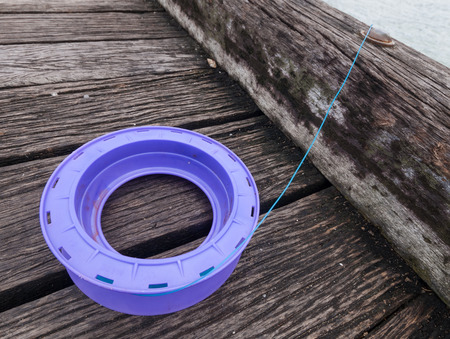 fishing rig: A purple plastic handline and blue fishing line, setup on a wooden jetty waiting for a fish.