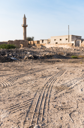 ras: United Arab Emirates, Ras Al Khaimah, 04112015, Tyre tracks and mosque tower at Old Ras Al Khaimah abandoned ghost town, Al Jazirah Al Hamra Editorial
