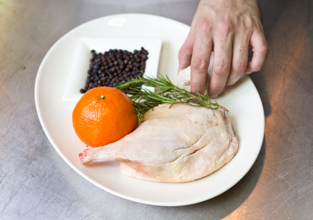 free range: Free range raw duck leg, with herbs, orange and garlic, on a white plate. Duck wellington step by step.