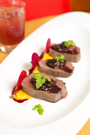 step well: Organic Venison served with fresh raspberry raspberry sauce, beetroot slices and pumpkin puree, on a white plate. Stock Photo