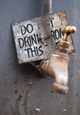 Dirty water tap, with a warning not to drink the water. Water is unsafe for consumption.