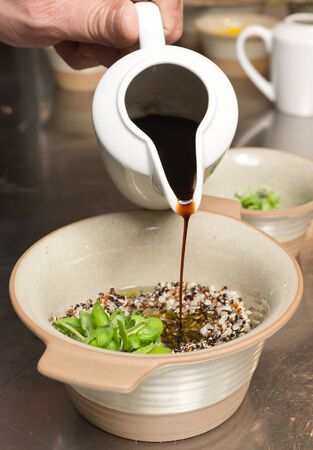 poured: Balsamic vinegar being poured into a rustic bowl of Organic quinoa