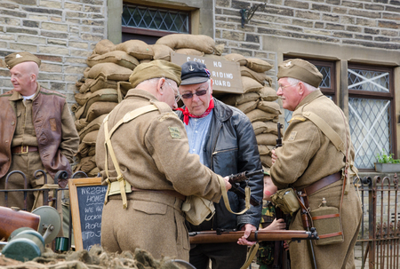 take a history: Yorkshire, England, 05152015, An group of older british war veteran soldiers checking weapons, from the home guard, with a beret hats and uniform. Howarth 1940s weekend