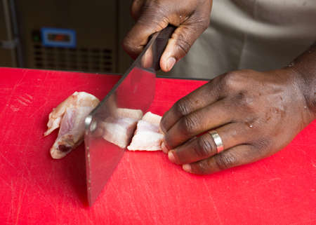 free range: A cleaver slicing through free range raw chicken wings on a red cutting board.