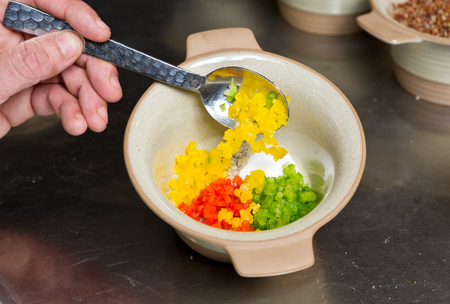 diced: Diced red, yellow and green peppers being placed into a rustic ceramic bowl in a kitchen.