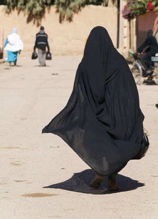 burqa: A woman in a burka Burqa walking down a middle eastern street Stock Photo