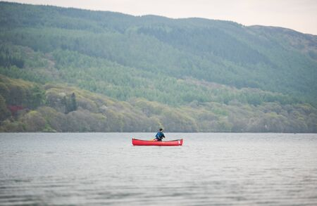 canoeist: Lake Coniston, England, 06062016, A lonely canoeist  on lake coniston, The Lake District, with a foggy green forest backdrop. Editorial