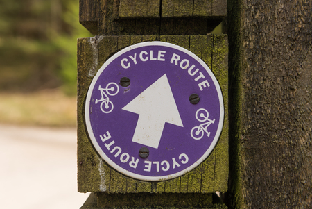 a public notice: Cycle bicycle route signs on a wooden post in a forest.