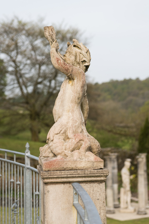 hand carved: A hand carved cherub blowing a horn. A roman style stone carved statue, on a stone base Stock Photo