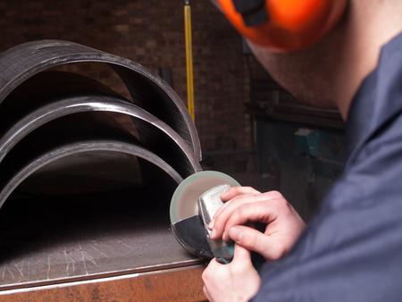 grind: A man in a workshop using an industrial metal grinder to grind down stainless steel, creating vibrant orange sparks
