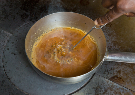 A hand whisk, whisking a pan of boiling hot chicken gravy made from the stock of a fresh organic chicken.