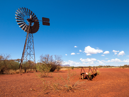 an old rusty wind turbine and cattle feeder,  in the harsh arid red landscape of the australian outback bush.