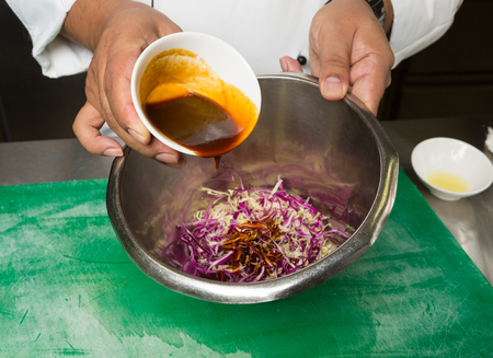 freshly prepared: spicy barbecue sauce being poured and mixed, into a bowl, of freshly prepared homemade coleslaw.