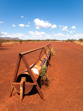 an old rusty cattle feeder,  in the harsh arid red landscape of the australian outback bush. Stock Photo