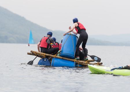 Lago Coniston, Inghilterra, il 06/06/2016, un gruppo di uomini su una zattera improvvisata, sul lago Coniston, il distretto del lago. Esercizio di team building