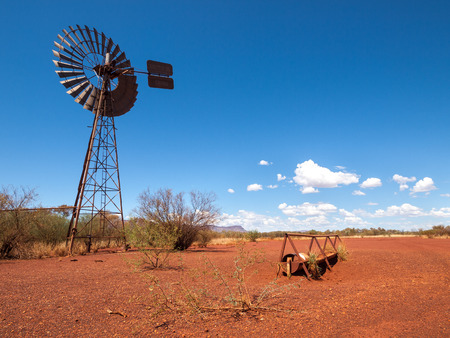 australian outback: an old rusty wind turbine and cattle feeder,  in the harsh arid red landscape of the australian outback bush.
