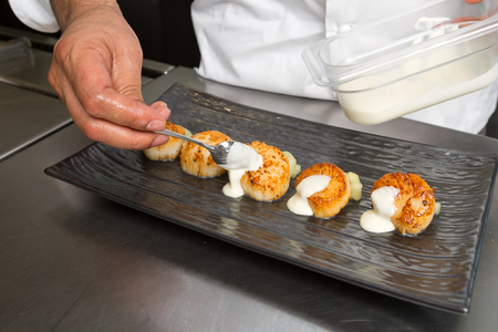 fished: Delicious pan seared organic scallops, served with a white wine cream sauce. Presented professionally and shot with a shallow depth of field.