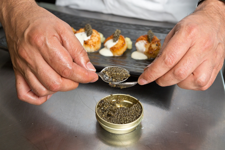 Caviar being measured by teaspoons, in preparation to be used as a topping for scallops,shot with a shallow depth of field. Stock Photo