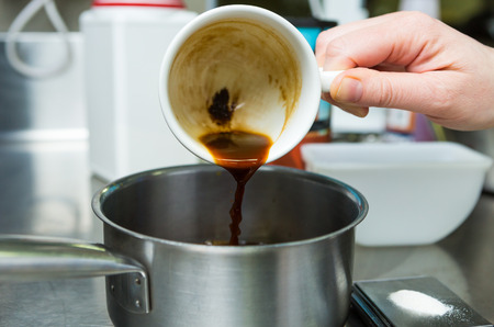 Rich strong italian espresso coffee being poured into a metal pan ready for boiling.