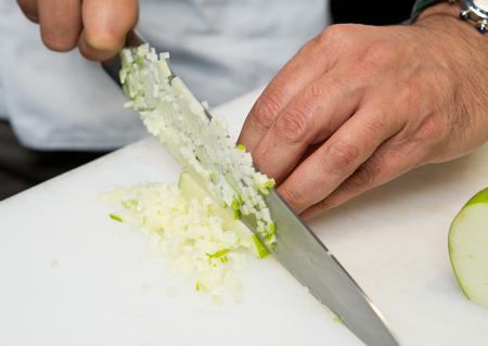 A knife cutting thin cubes of fresh organic green apple, on a white cutting board.
