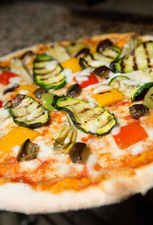 digest: Close up of a Vegetarian thin crust  pizza, with grilled courgette, peppers, aubergine, artichoke, cheese and tomato topping Stock Photo