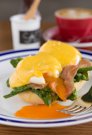 Eggs benedict and fresh salmon serves on a lightly toasted muffin served with hollandaise sauce and a coffee.