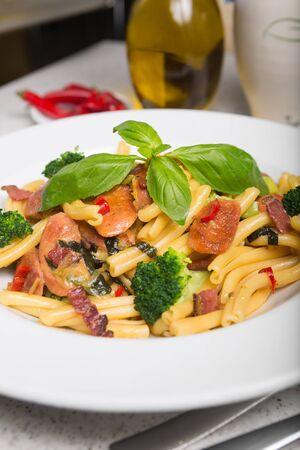 italian sausage: A delicious fresh gourmet Italian strozzapreti pasta dish, with pancetta, italian sausage, broccoli, vegetables, topped with fresh basil.