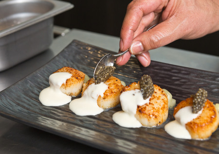 Delicious pan seared organic scallops, served with caviar, and white wine cream sauce. Presented professionally and shot with a shallow depth of field.