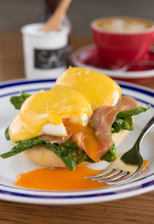 benedict: Eggs benedict and fresh salmon serves on a lightly toasted muffin served with hollandaise sauce and a coffee.