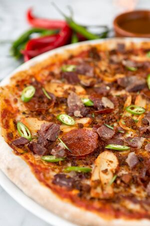Spicy pepperoni, chicken and bacon pizza with jalapeno slices Stock Photo