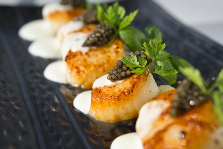 Delicious pan seared organic scallops, served with celery puree, caviar, parsley and white wine cream sauce. Presented professionally and shot with a shallow depth of field.