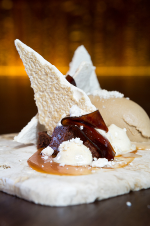 Finest Italian Coffee espresso jelly strips, served on a sweet Meringue bed, with chocolate and toffee crumble, salted toffee sauce and ice cream. Stock Photo