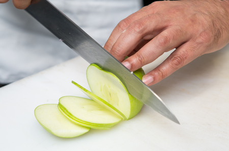 A knife slicing thin slices of fresh organic green apple, on a white cutting board. Stock Photo