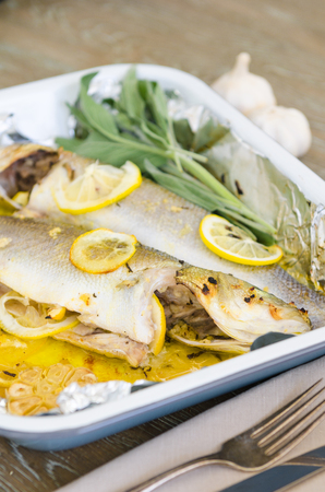 Fresh oven roasted sea bass fish, with roasted lemon slices and roasted garlic bulbs, served in a metal baking tray. Stock Photo