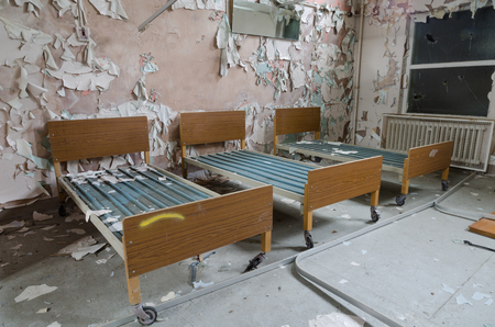 Three old hospital beds in an abandoned hospital ward.