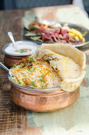 exotically: Authentic chicken biryani served with naan bread, fragrant pilau rice and yoghurt, in a metal pot. Stock Photo