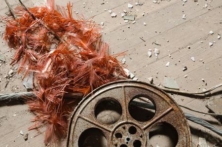 pacientes: Un antiguo carrete de película de cinematografía oxidada y metálica, que ha quedado en un cine abandonado entre restos de hormigón.