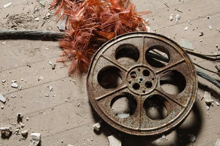 An old metal rusty cinematography cinema film reel, that has been left in an abandoned cinema amongst concrete debris. Stock Photo