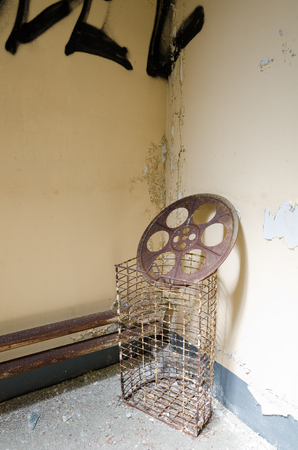 An old abandoned rusty  cinema film reel, in a decaying forgotten cinema movie theatre building.The end of film production. Stock Photo