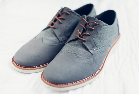 brogues: A beautiful pair of grey wedding shoes with an orange finish in the laces and sole. All shot with a creative shallow depth of field on a soft delicate white backdrop.