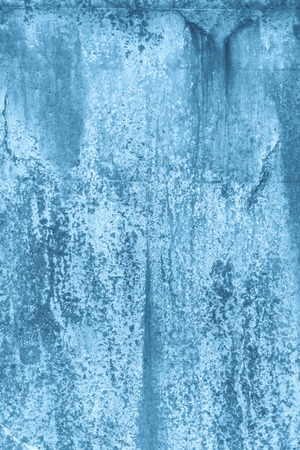 A rustic rough industrial raw concrete textured wall coloured blue.